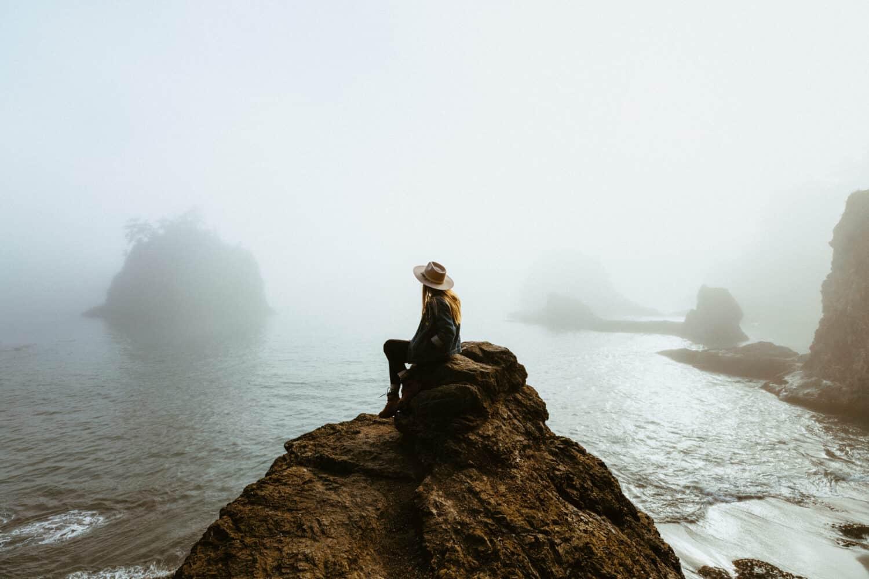 Emily Mandagie se sienta sobre una roca en la costa de Oregón - Noroeste del Pacífico